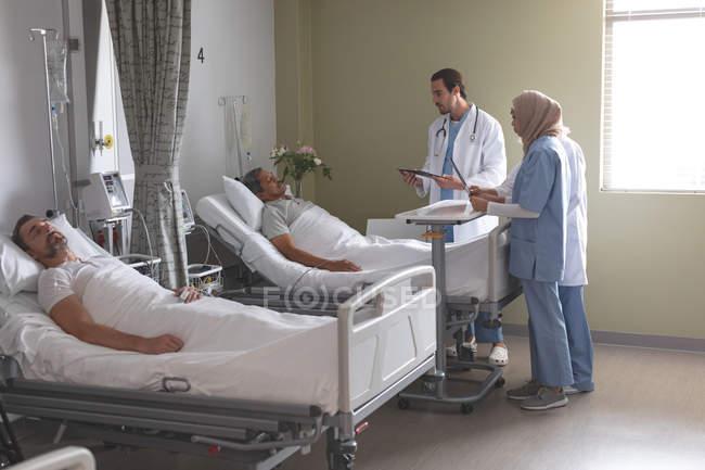 Побочный обзор различных врачей, взаимодействующих со старшим пациентом смешанной расы, в то время как белый мужчина спит рядом с ним в палате больницы — стоковое фото