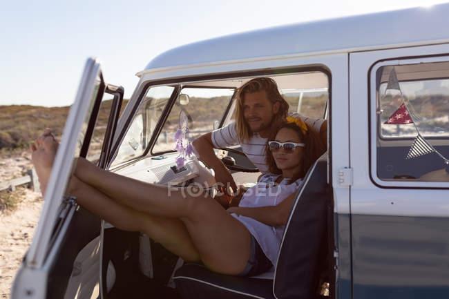Вид спереди молодой пары, расслабляющейся и отводящей взгляд в фургоне на пляже — стоковое фото