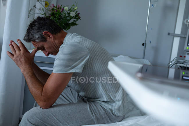 Side view of worried Caucasian male patient sitting on bed with elbows on the knee in the ward in hospital — Stock Photo