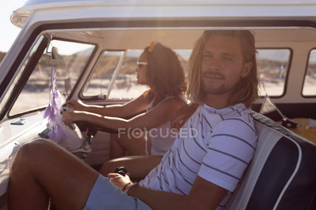 Вид сбоку на молодую разнородную пару, сидящую вместе на передних сиденьях фургона на пляже — стоковое фото