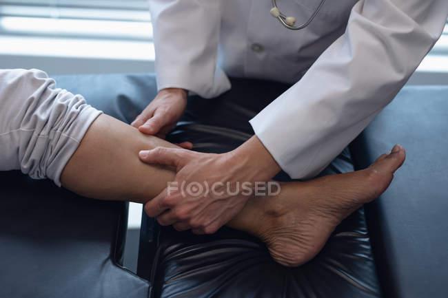 Close-up de médico feminino examinando sua perna paciente no hospital — Fotografia de Stock