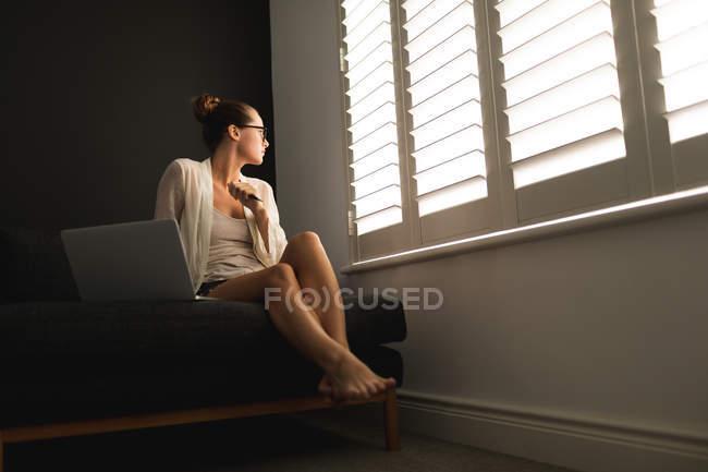 Вид сбоку кавказской женщины, смотряй через окно при использовании ноутбука в гостиной дома — стоковое фото