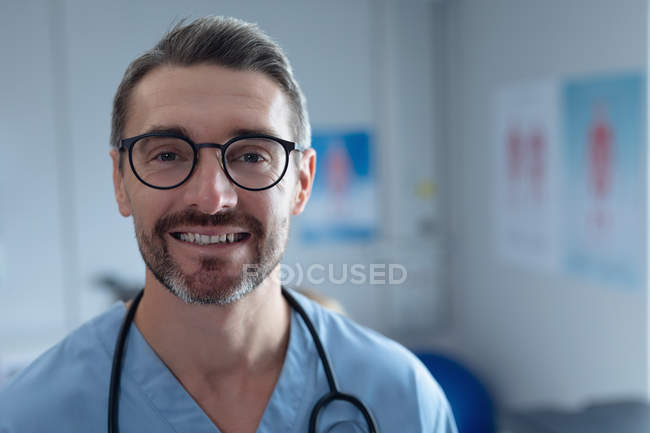 Portrait of mature Caucasian male surgeon with stethoscope around the neck looking at camera in hospital — Stock Photo