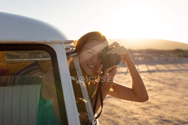 Front view of young Caucasian woman taking picture with digital camera out of window of a camper van — Stock Photo