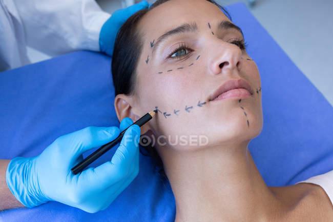 Nahaufnahme eines männlichen Chirurgen, der das Gesicht einer hübschen kaukasischen Frau vor einer plastischen Operation im Krankenhaus markiert — Stockfoto