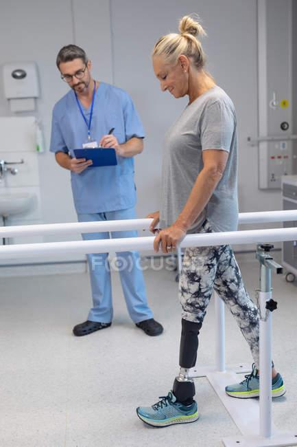 Seitenansicht eines kaukasischen männlichen Physiotherapeuten, der auf Klemmbrett schreibt, und einer kaukasischen Patientin, die amputiert ist und parallel im Krankenhaus läuft — Stockfoto
