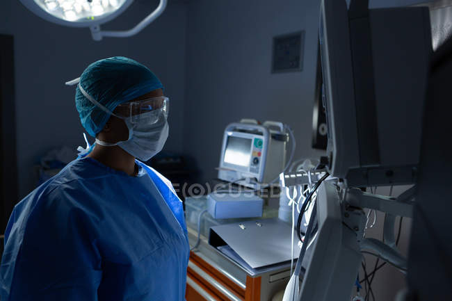 Side view of young mixed race female surgeon looking at monitor in operation theater. Surgeon wears surgical mask, gloves, gown, cap, an protective eyewear. — Stock Photo