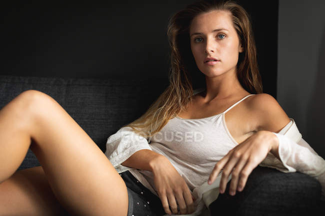 Portrait of Caucasian woman relaxing on a sofa in living room at home — Stock Photo
