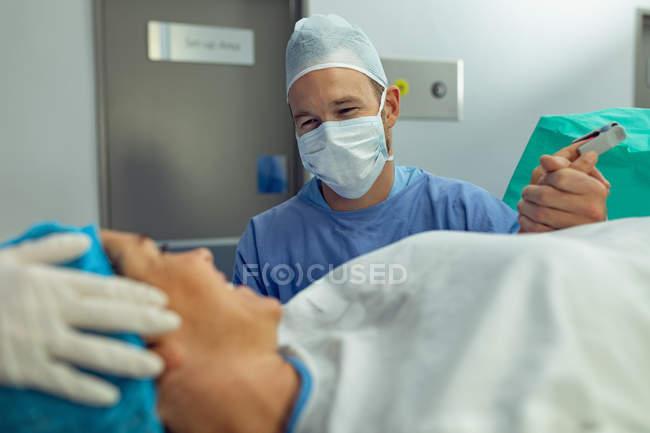 Vorderansicht eines kaukasischen Mannes, der schwangere Frau während der Wehen im Operationssaal des Krankenhauses tröstet — Stockfoto