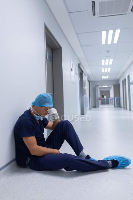 Vista lateral de um belo cirurgião caucasiano tenso, com a mão sobre o rosto sentado no corredor do hospital. Cirurgião está usando máscara cirúrgica, boné cirúrgico, vestido e luvas cirúrgicas . — Fotografia de Stock
