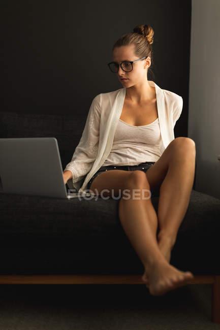 Vista frontale della donna caucasica che utilizza il computer portatile su un divano in soggiorno a casa — Foto stock