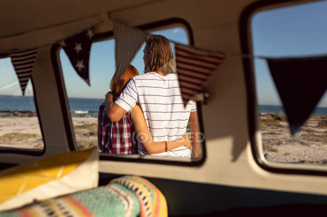 Rear view of Caucasian couple with arms around standing together near camper van at beach — Stock Photo