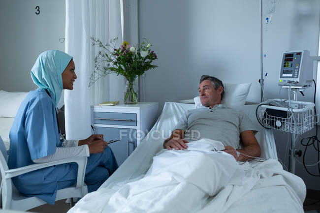 Front view of mixed race female doctor in hijab interacting with Caucasian male patient in the ward in hospital — Stock Photo
