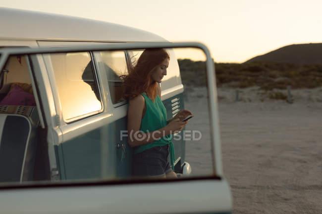 Вид збоку красива кавказька жінка спираючись на кемпер Ван і за допомогою мобільного телефону на пляжі — стокове фото
