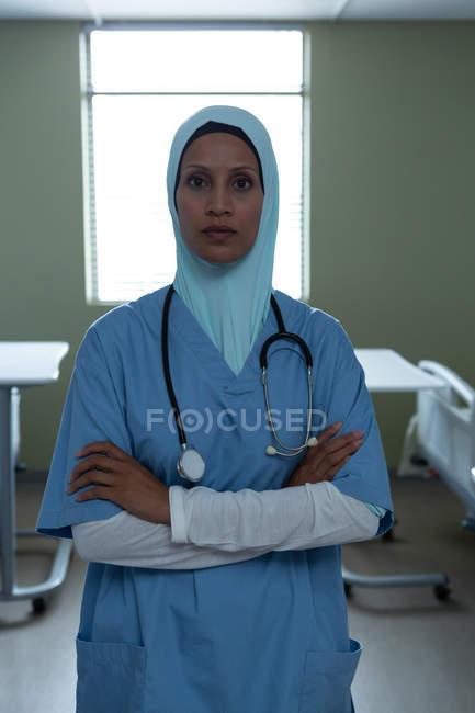 Retrato de bela mestiça médica feminina em hijab de pé com os braços cruzados e estetoscópio em torno de seu pescoço no hospital — Fotografia de Stock