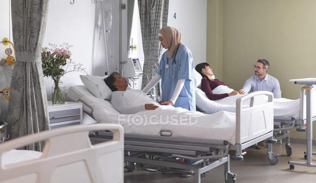 Frontansicht einer Krankenschwester mit gemischter Rasse, die mit einer Patientin interagiert, während verschiedene Paare neben ihnen auf der Station im Krankenhaus stehen. — Stockfoto