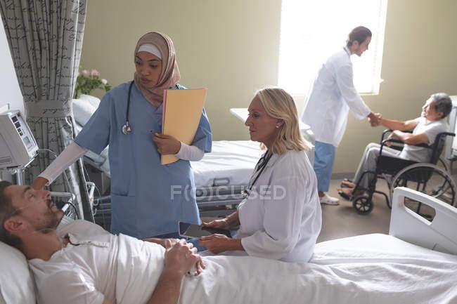 Vista frontale di diverse donne che interagiscono con pazienti maschi caucasici nel reparto ospedaliero. Sullo sfondo medico maschio caucasico sta stringendo la mano di disabile anziano paziente di razza mista maschile in sedia a rotelle . — Foto stock