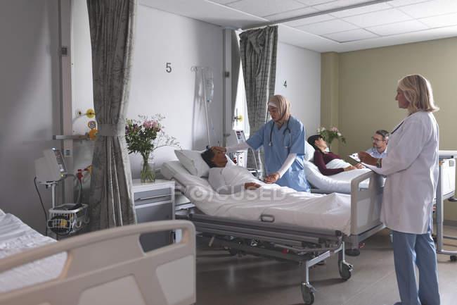 Frontansicht diverser Ärztinnen, die mit gemischtgeschlechtlichen Patientinnen auf der Krankenstation interagieren. im Hintergrund hält ein kaukasischer Mann die Hand einer asiatischen Frau, die im Krankenhaus im Bett liegt. — Stockfoto