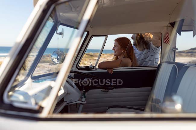 Вид сбоку счастливой молодой кавказской пары, отводящей взгляд от фургона Camper на пляже — стоковое фото