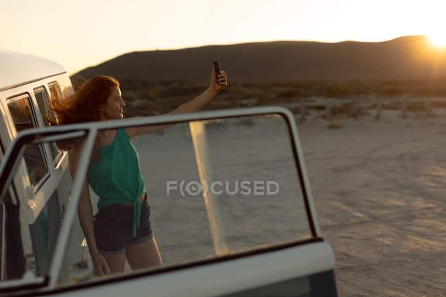 Side view of beautiful young Caucasian woman taking selfie near camper van at beach — Stock Photo