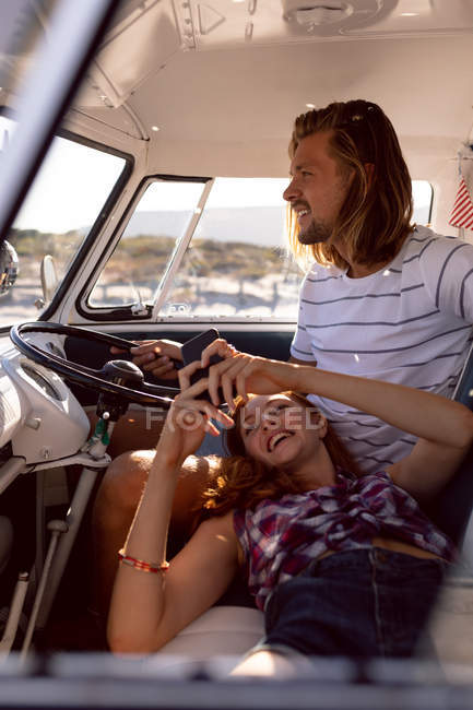 Front view of beautiful Caucasian woman using mobile phone while lying on man's lap in front seat of camper van at beach — Stock Photo