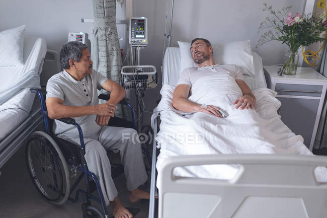 Front view of diverse male patients interacting with each other in the ward at hospital.Caucasian male patient lying in bed while mixed-race patient sits in wheelchair. — Stock Photo