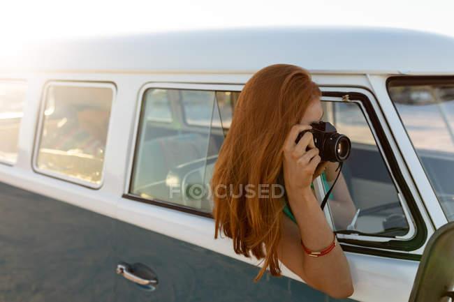 Vue latérale d'une jeune femme caucasienne prenant une photo avec un appareil photo numérique par la fenêtre d'un camping-car — Photo de stock