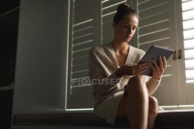 Низкий угол зрения кавказской женщины с помощью цифрового планшета, сидя на сиденье у окна дома — стоковое фото