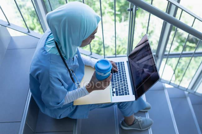 Вид женщины-врача смешанной расы в хиджабе с ноутбуком во время чашечки кофе в больнице — стоковое фото