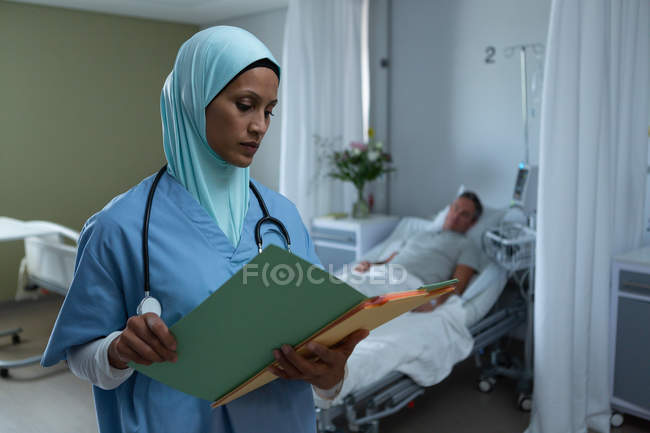 Frontansicht einer gemischten Rasse Ärztin mit Hijab, die sich medizinische Berichte ansieht, während ein kaukasischer männlicher Patient auf der Station im Krankenhaus im Bett schläft — Stockfoto