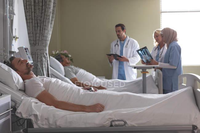 Vista laterale di diversi medici che interagiscono con pazienti maschi di razza mista mentre pazienti maschi caucasici dormono nel letto accanto a loro nel reparto dell'ospedale . — Foto stock