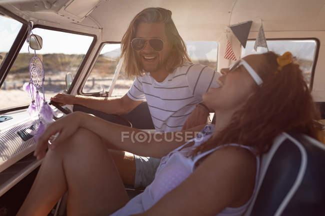 Боковий вид щасливих молодих різноманітна пара веселяться в передній сидіння Ван на пляжі — стокове фото