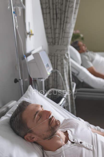 Seitenansicht eines kaukasischen männlichen Patienten, der auf der Krankenstation im Bett schläft. im Hintergrund ein älterer Mischlingspatient, der im Bett liegt. — Stockfoto