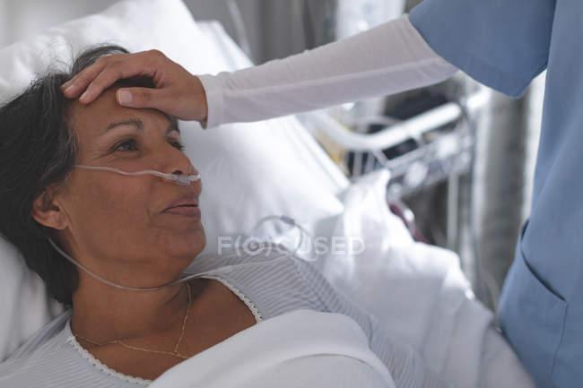 Primer plano de la enfermera de raza mixta comprobando la temperatura de la paciente de raza mixta a mano en la sala del hospital - foto de stock