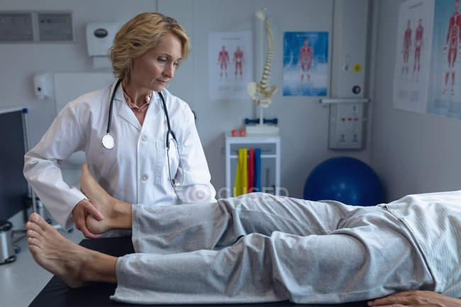 Vista dianteira do doutor fêmea caucasiano que examina o paciente masculino para trás no hospital — Fotografia de Stock
