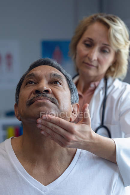 Front view of Caucasian female doctor examining mixed-race male patient neck in hospital — Stock Photo