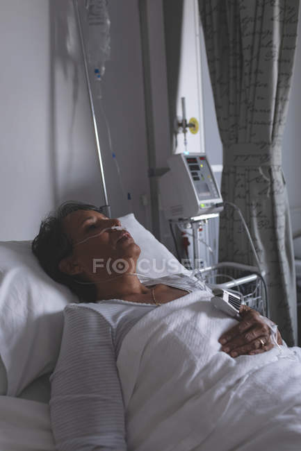 Front view of mature mixed-race female patient sleeping in bed in the ward at hospital — Stock Photo