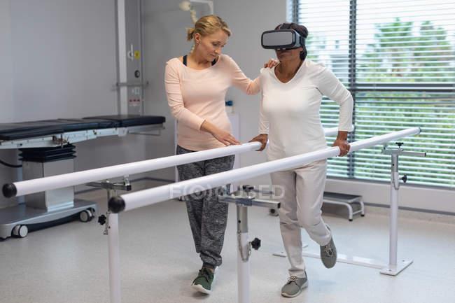 Seitenansicht der kaukasischen Patientin mit Virtual-Reality-Headset, während kaukasische Physiotherapeutin hilft ihr, mit parallelen Bars im Krankenhaus zu gehen — Stockfoto