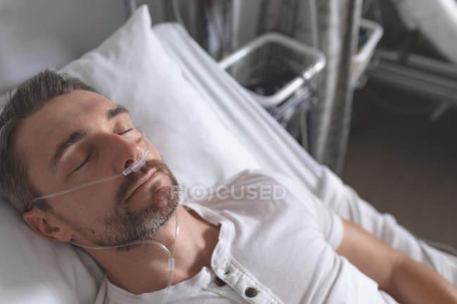 Vista frontal del paciente varón caucásico que duerme en la cama en la sala del hospital . - foto de stock