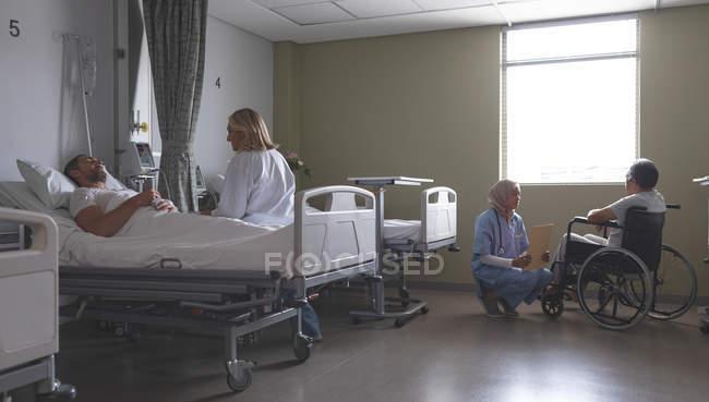 Вид сбоку на кавказскую женщину-врача, взаимодействующую с кавказской пациенткой, лежащей в палате больницы. Медсестра смешанной расы в хиджабе обсуждает медицинскую папку со старшим пациентом смешанной расы в инвалидном кресле рядом с окном . — стоковое фото