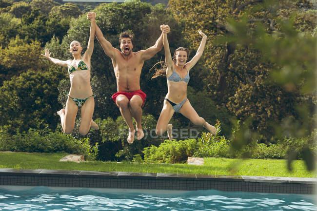 Вид спереди веселых кавказских мужчин и женщин, прыгающих в бассейн на заднем дворе — стоковое фото