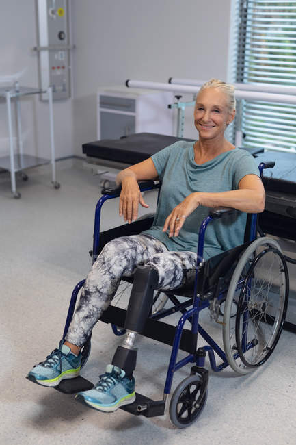 Front view of happy disabled Caucasian female patient looking at camera in wheelchair in the hospital — Stock Photo