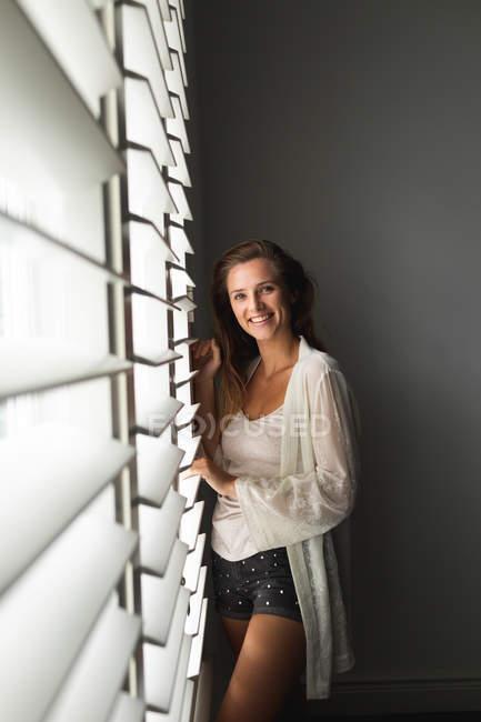 Портрет кавказской женщины, стоящей у окна вслепую дома — стоковое фото