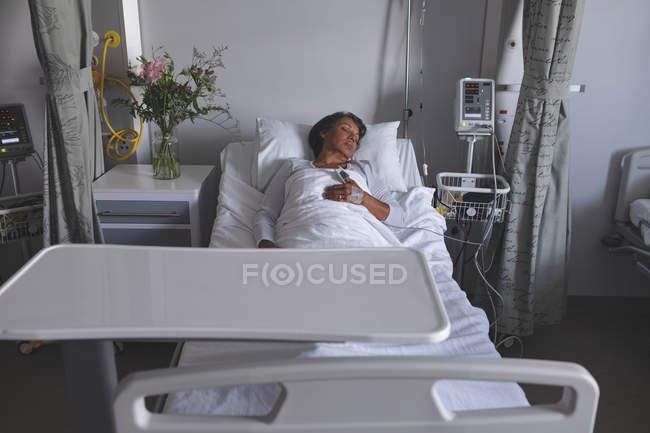 Вид спереди на взрослую пациентку смешанной расы, спящую в постели с одной рукой на животе в палате больницы. Цветы, медицинский монитор и шкаф стоят рядом с ее кроватью . — стоковое фото