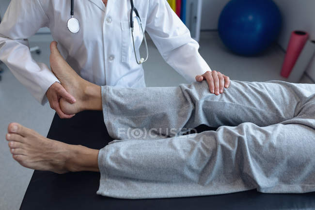 Mid section of female doctor examining male patient back in hospital — Stock Photo