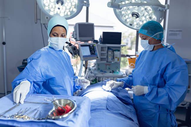 Vue latérale de divers chirurgiens pratiquant une chirurgie en salle d'opération à l'hôpital — Photo de stock