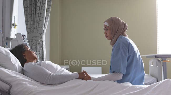 Side view of beautiful mixed-race female doctor consoling mixed-race female patient in the ward. Mixed-race female patient is lying in bed at the ward. — Stock Photo