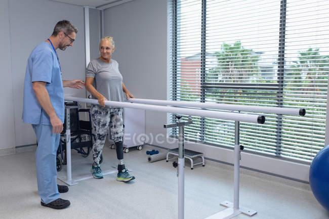 Вид сбоку кавказского физиотерапевта-мужчины, помогающего пациенту ходить с параллельными решетками в больнице — стоковое фото