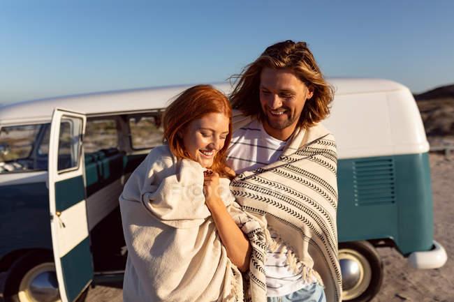 Вид з днем молоді кавказька пара загорнуті в ковдру поблизу кемпер Ван на пляжі — стокове фото