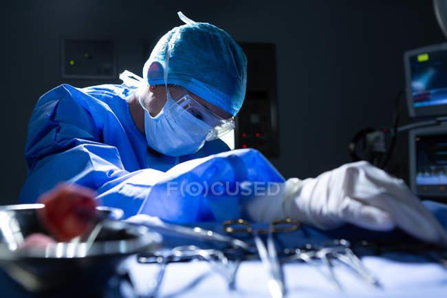 Vue avant de jeune chirurgien féminin de course mélangée retenant des instruments chirurgicaux tout en exécutant l'opération dans le théâtre d'opération à l'hôpital — Photo de stock